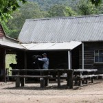 Camera operator outside the Cattleman's Huts